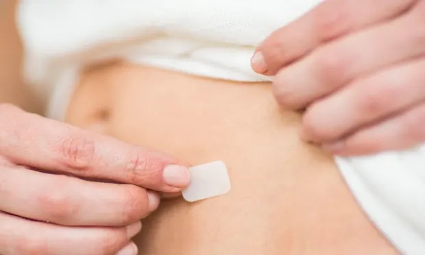 A woman applying an HRT patch