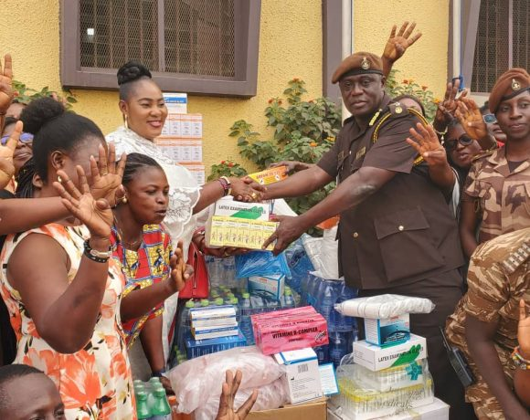 Nana Ama Ampomah, Ashanti Regional Women's Organiser of the New Patriotic Party presents some of the items to a Prisons Officer on Val's day.