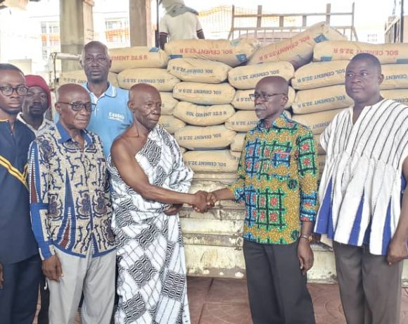 Nana Abebrese, aide to Manhyia South MP presenting the bags of cement to Okyeame Yamoah Gyamfi, chief linguist to Mawerehene